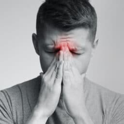 Sinus pain, sinusitis. Sad man holding his nose, black and white photo with red sore zone